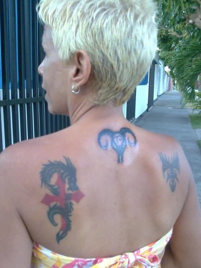 Women Show Aries Back Tattoo And Dragon With Cross