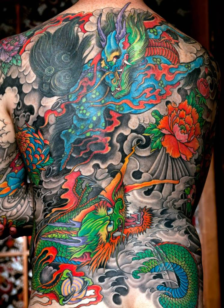 Men Show Awesome Colorful Asian Dragon Fight Tattoo On Back