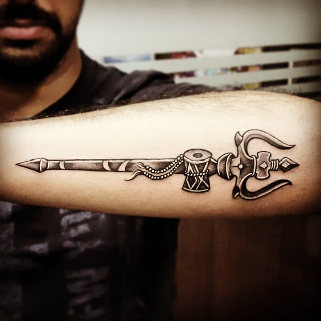 Amazing Traditional Trishul And Pellet Drum Tattoo On Forearm