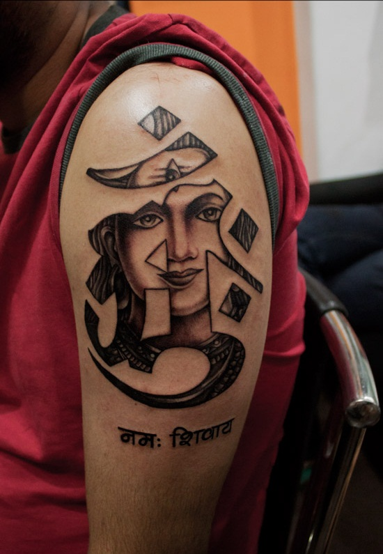 Outstanding Om Sign And Buddha Face Tattoo On Men Shoulder