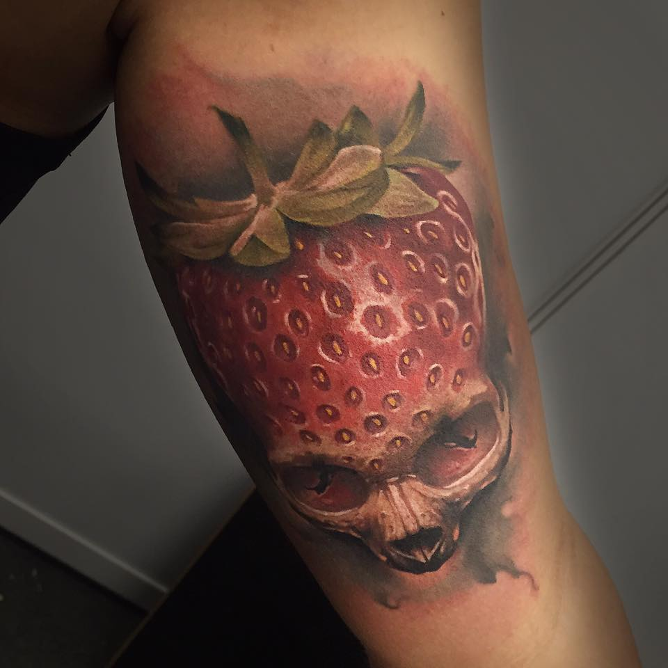 Awesome 3D Strawberry Skull Tattoo On Left Bicep By Benjamin Laukis