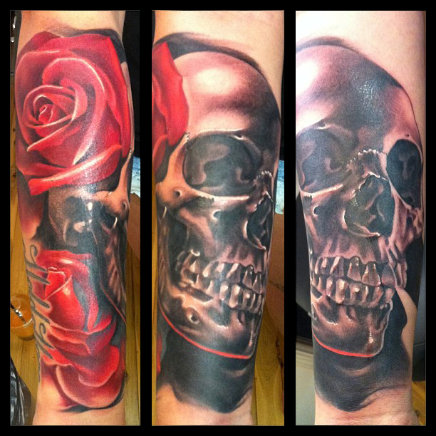 Black Ink Skull With Two Red Roses Tattoo On Arm By Fabz