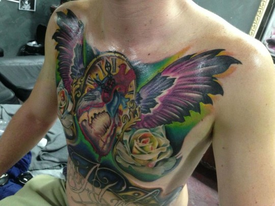 Traditional Real Heart With Wings And Clock Tattoo On Man Chest By Fabz