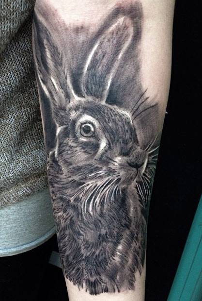 Black hairy rabbit tattoo on arm