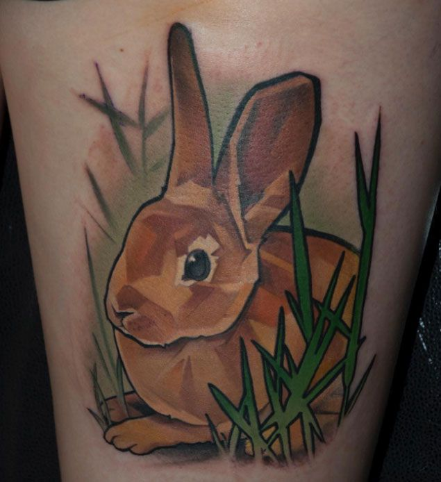 Fabulous rabbit tattoo in grass on thigh