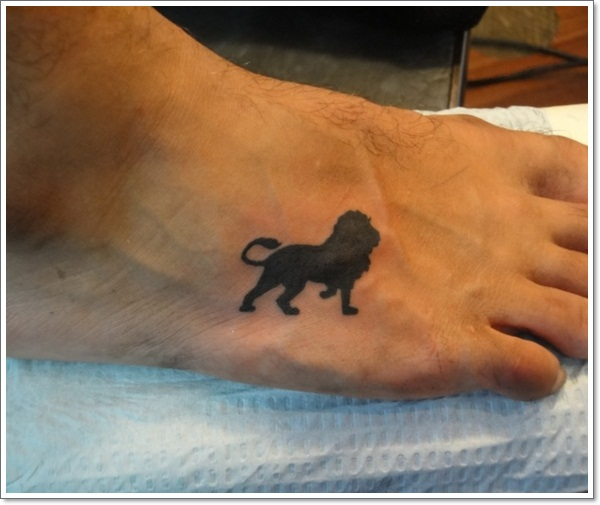 Small lion tattoo on foot in black color