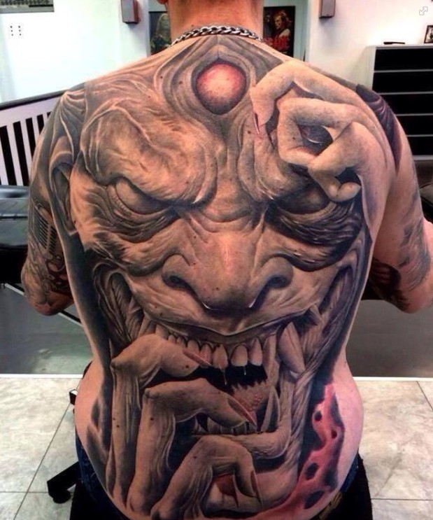 Frightning devil tattoo with big teeth on back inked color