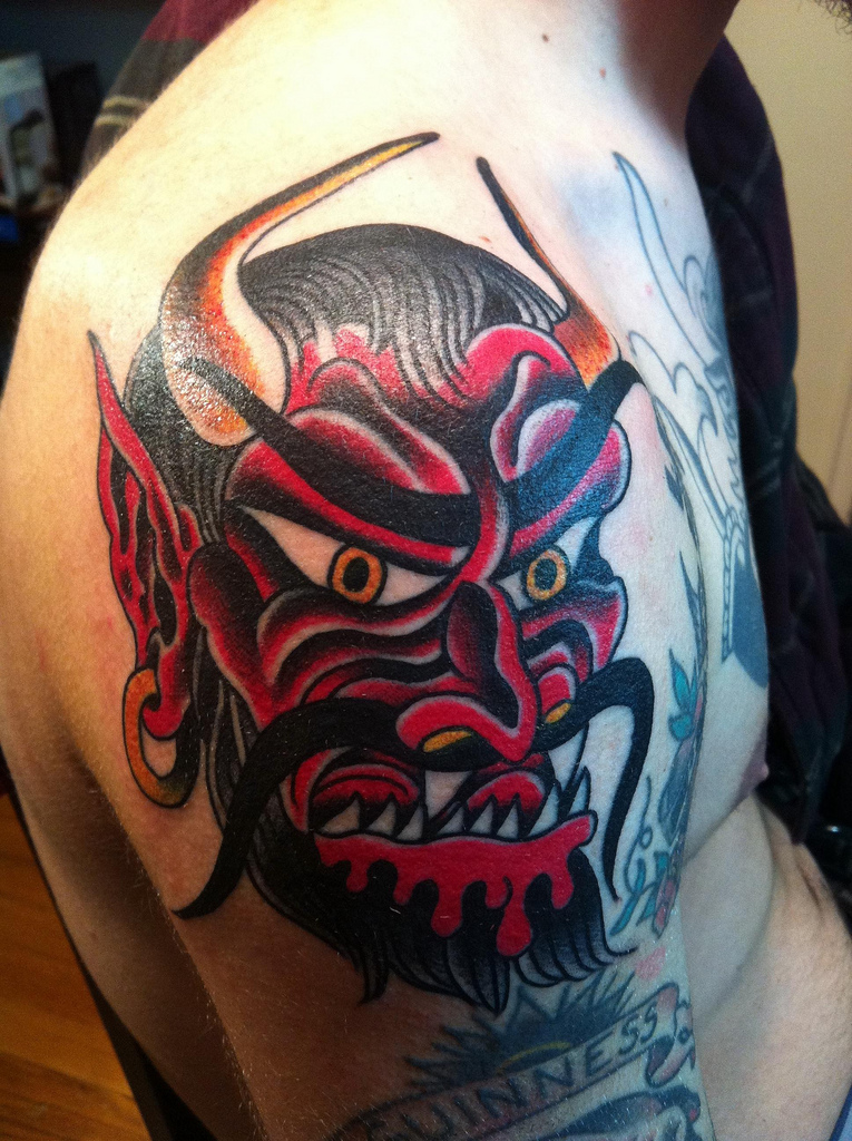 Hnngry devil tattoo inked red and black on arm