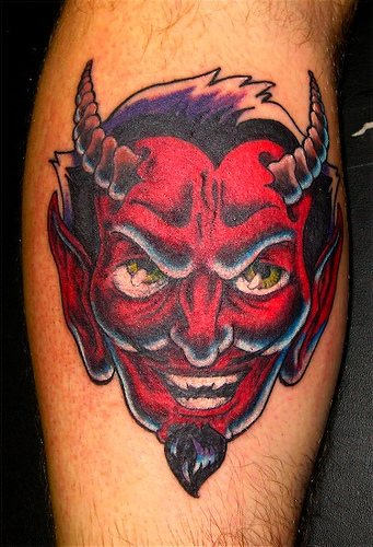 Real devil tattoo in red color on leg