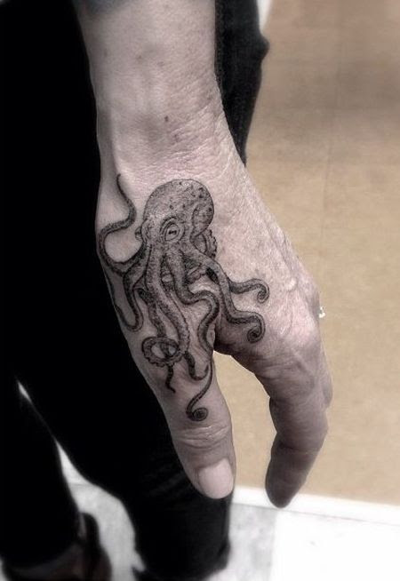 cute octopus tattoo above thumb in grey color